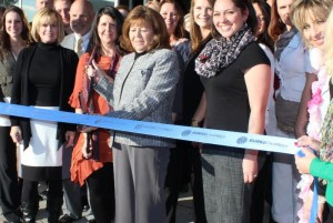 Founder Hope Lowman cuts the ribbon as CEO Wendy Ward (to her left), staff and guests celebrate the opening of the staffing firm's fourth office.